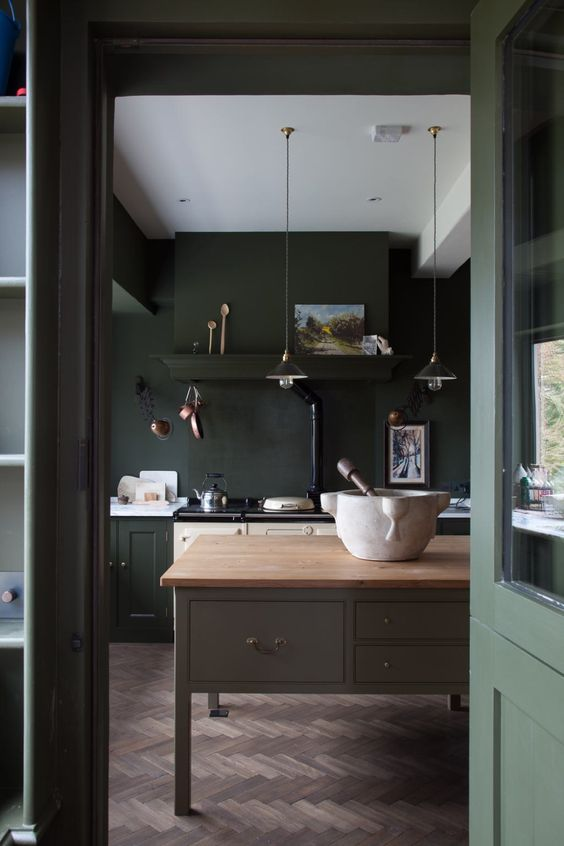 a vintage moody kitchen in dark green and lighter shades of green, a grey kitchen island with a wooden countertop and pendant lamps