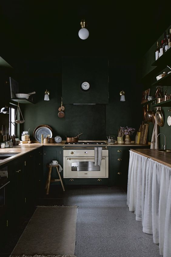 a vintage moody kitchen with black walls and cabinetry, wooden countertops, lamps and a kitchen island with a curtain