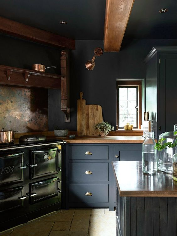a vintage moody kitchen with graphite grey cabinetry, a black hearth and wooden countertops plus wooden beams on the ceiling