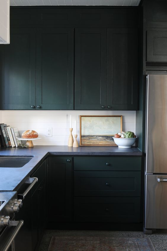a vintage moody kitchen with sleek dark cabinetry, a grey stone countertop, a white tile backsplash and some art