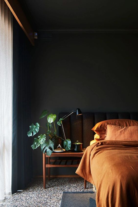 a welcoming moody bedroom with black walls and a bed, with wooden nightstands, rust colored bedding and black curtains