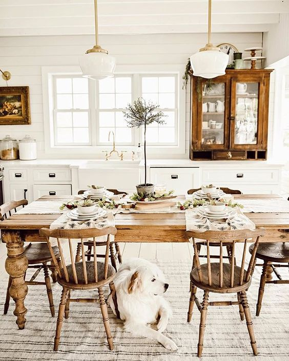 a white farmhouse kitchen with vintage wooden cabinets, a vintage wooden table, chairs and pendant lamps plus artworks