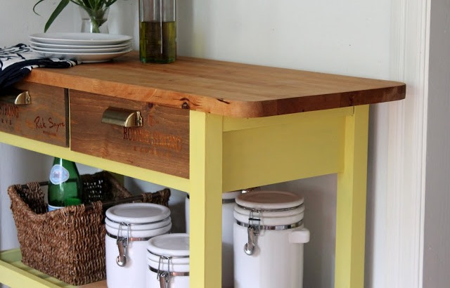 an IKEA Forhoja cart painted yellow, with a stained wooden countertop and wine crate drawer fronts is a bold idea to rock