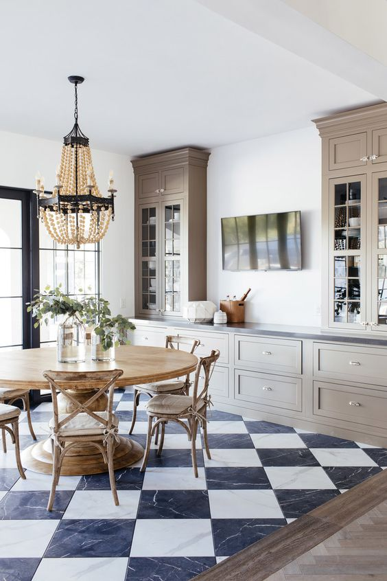 an elegant farmhouse kitchen with taupe cabinets, a rustic dining space with a round table and chairs of wood is very cozy