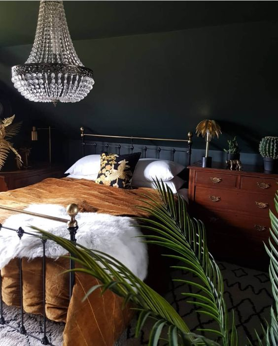 an elegant moody bedroom with a metal bed, a woodne nightstand, a statement crystal chandelier and potted plants