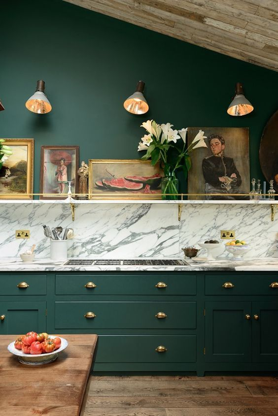 an elegant moody kitchen with hunter green walls and cabinetry, a marble backsplash, gold handles, a gallery wall on a ledge is very chic