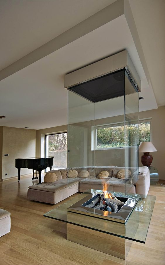 an ultra modern wood, metal and glass fireplace with a metal frame is a centerpiece of this room that makes it welcoming