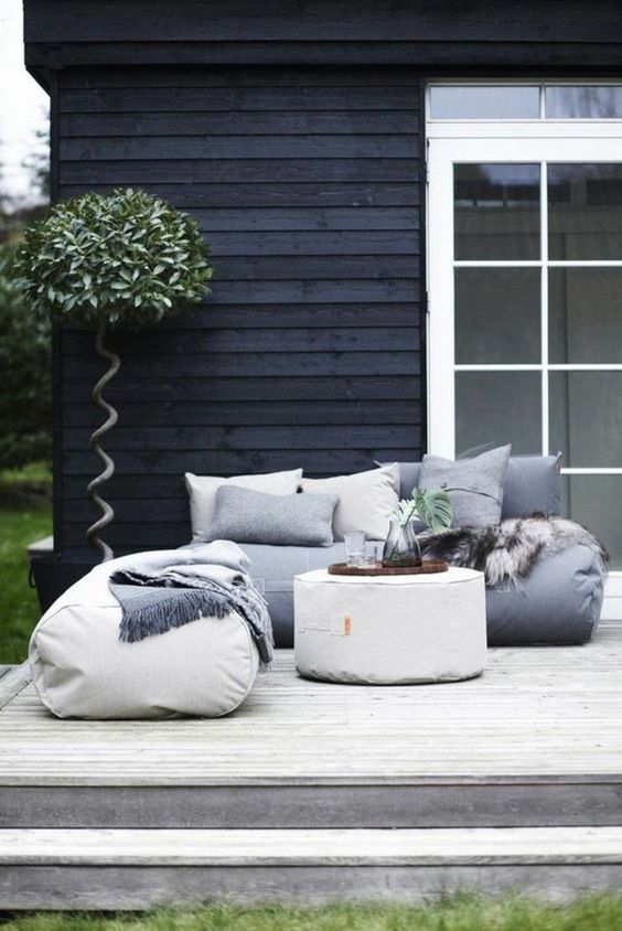 modern beanbag furniture and soft pillows plus some greenery make up a very cozy and welcoming setup for a modern scandinavian-inspired deck