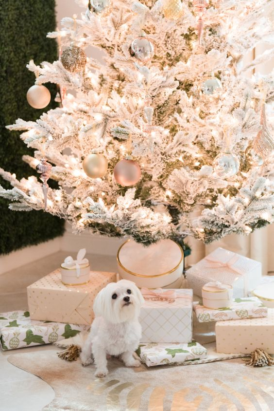 a flocked Christmas tree with shiny metallic, glitter and pastel ornaments, lots of white and blush gift boxes and a white dog
