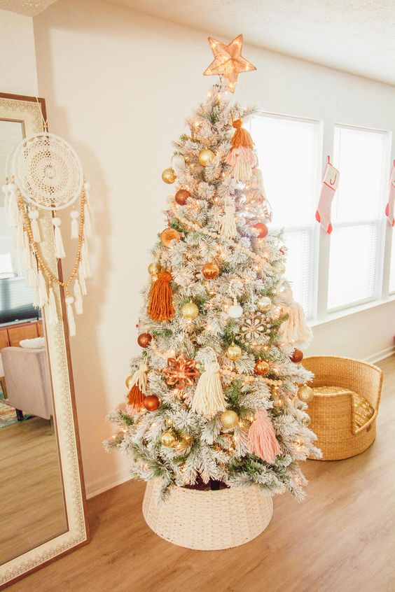 a lovely flocked Christmas tree with pastel boho decor, orange, gold and blush ornaments, beadsm large tassels and lights