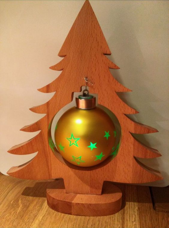 a tabletop plywood Christmas tree on a wooden stand with a single large ornament is a cool idea for some small space