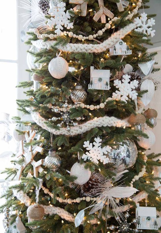 super chic Christmas tree decor with woven and bead garlands, snowflakes and houses, feathers and twine and knit ornaments