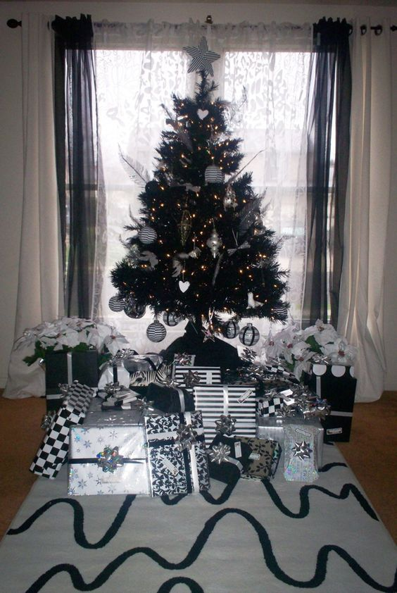 a black Christmas tree with lights, black and white ornaments, ornaments shaped as hearts and stars, feathers and piles of Christmas gifts