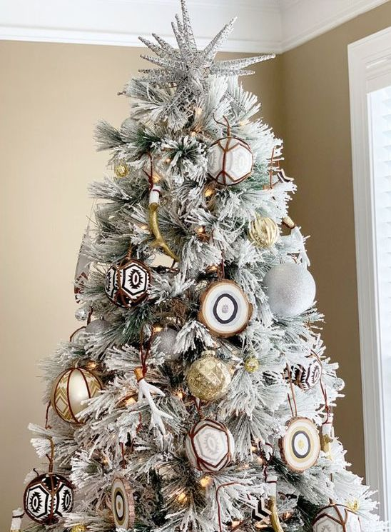 a flocked Christmas tree with white glitter ornaments, gold ones, agate slices and gold antlers plus lights is very free-spirited