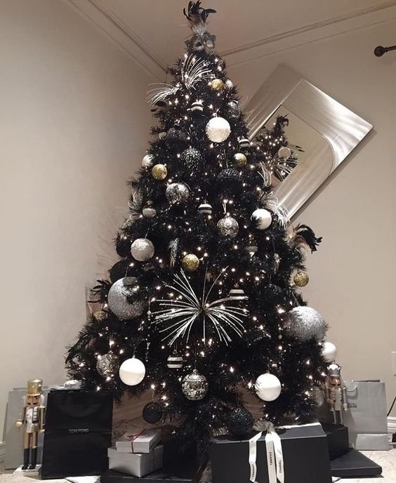 a black Christmas tree with lights, white, silver and black ornaments, silver touches and ribbons is pure glam and chic