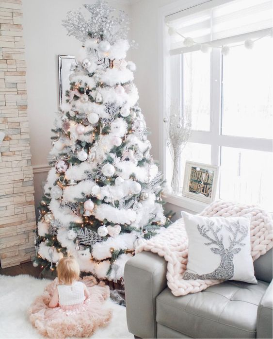 a flocked Christmas tree decorated with faux fur, silver leaves and pearl and white ornaments is super chic