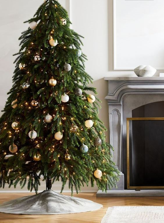 a Christmas tree with lights, white, grey and gold ornaments and a felt tree skirt looks very natural and modern
