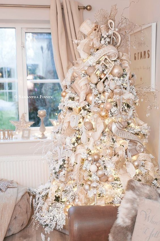 a beautiful flocked Christmas tree decorated with metallic ornaments, long ribbons and lights plus bows is all glam