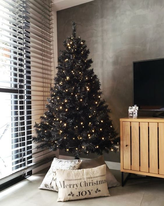 a black Christmas tree with only lights and pillows covering the base is a lovely and minimal idea for a modern space