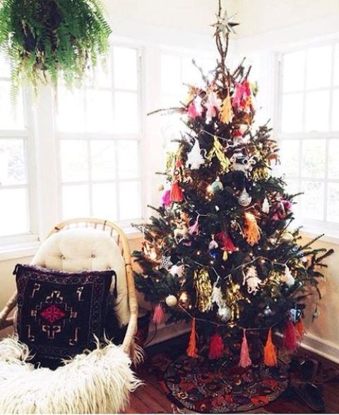 a colorful Christmas tree with lights, bright ornaments, colorful tassel garlands and a silver star on top