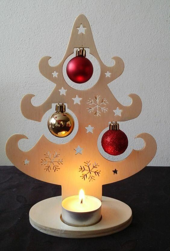 a creative plywood tabletop Christmas tree with cutout stars and snowflakes, red and gold ornaments and a little tealight