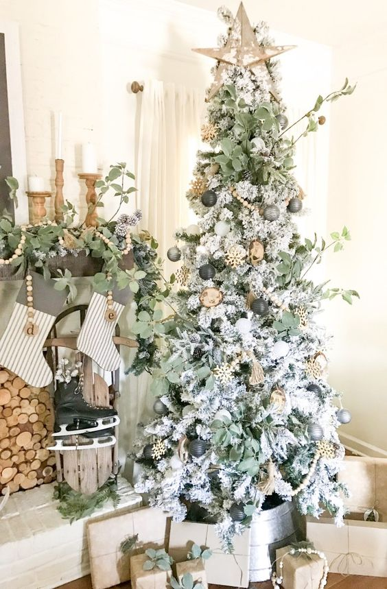 a boho Christmas tree with gold, grey and black ornaments, greenery, a wooden star on top and wooden beads and snowflakes