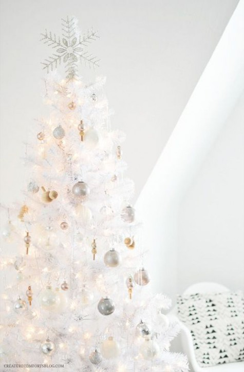 a pure white Christmas tree with lights, silver, gold and pearly ornaments and a pretty shiny snowflake tree topper