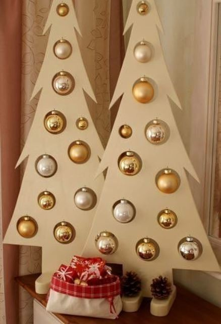 tan-colored plywood tabletop Christmas trees with lots of metallic ornaments hanging in the cutouts and some pinecones