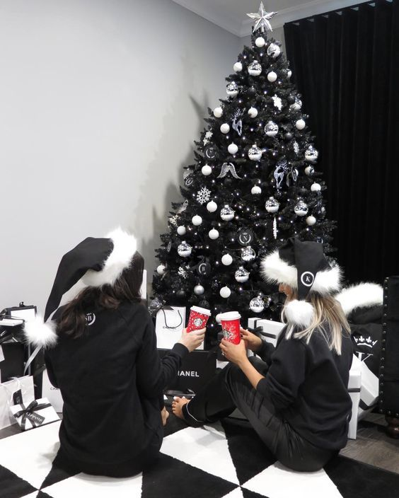 a black Christmas tree with white ornaments, snowlfkaes and ribbons and some lights is a lovely and chic idea