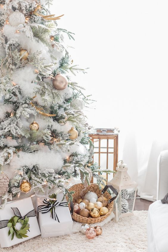 a flocked Christmas tree decorated with gold ornaments and antlers looks very fairy-tale like and very wild