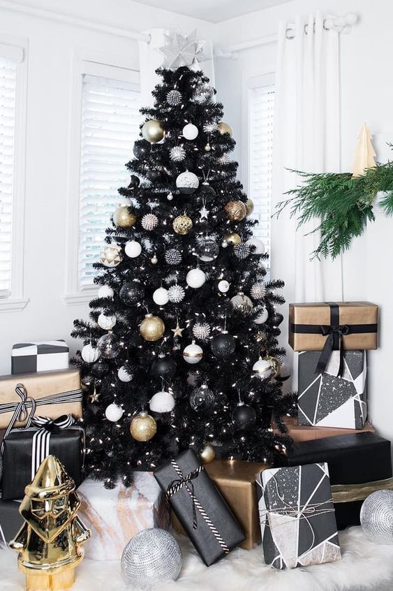 a black Christmas tree with white, sheer, gold and black ornaments and lights and piles of black and gold gifts under the tree