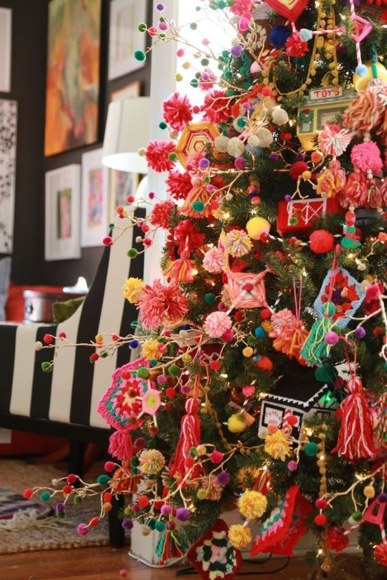 a super colorful Christmas tree decorated with bright pompom garlands and ornaments, with tassels, macrame and various yarn decor looks fun