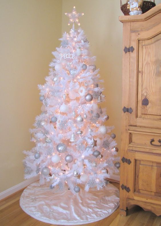 a white Christmas tree with lights, silver, white and shiny silver ornaments, a shiny star topper and some letters is wonderful
