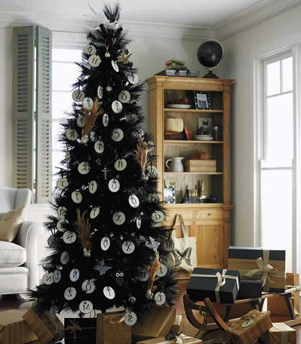a black feather Christmas tree with vintage letter ornaments and pampas grass plus gifts under it and on a sleigh
