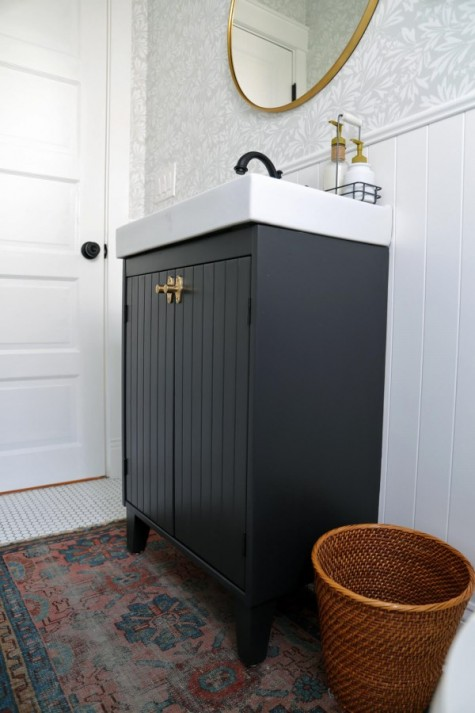 an Ikea Silveran vanity hacked with black paints and wood plus brass knobs is a very elegant solution for a rustic bathroom