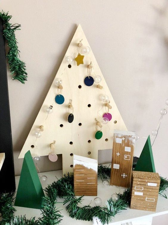 a plywood tabletop Christmas tree with perforations and colorful mini ornaments is a pretty idea for holidays