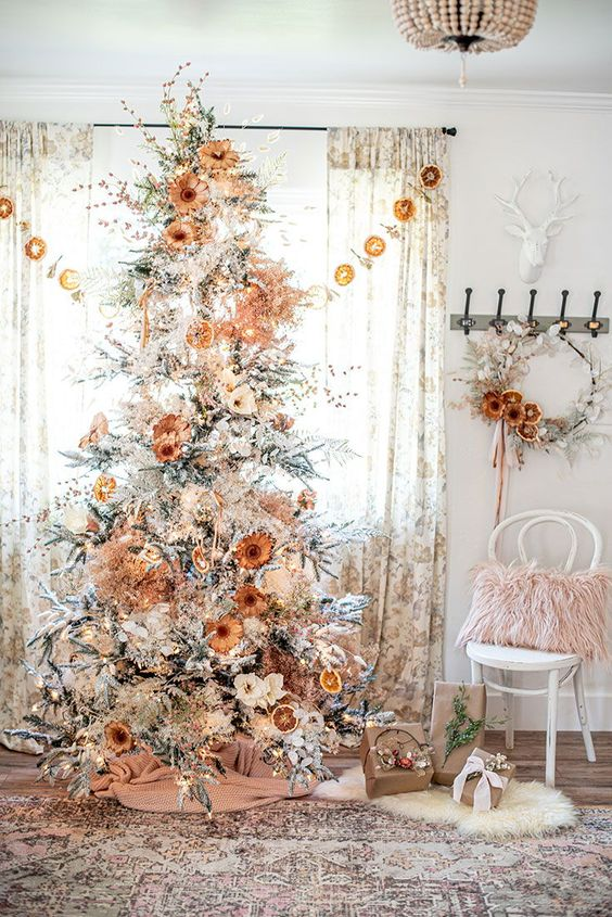a pretty boho natural Christmas tree decorated with lights, dried and fabric blooms, blooming branches and berries and some burlap at the base