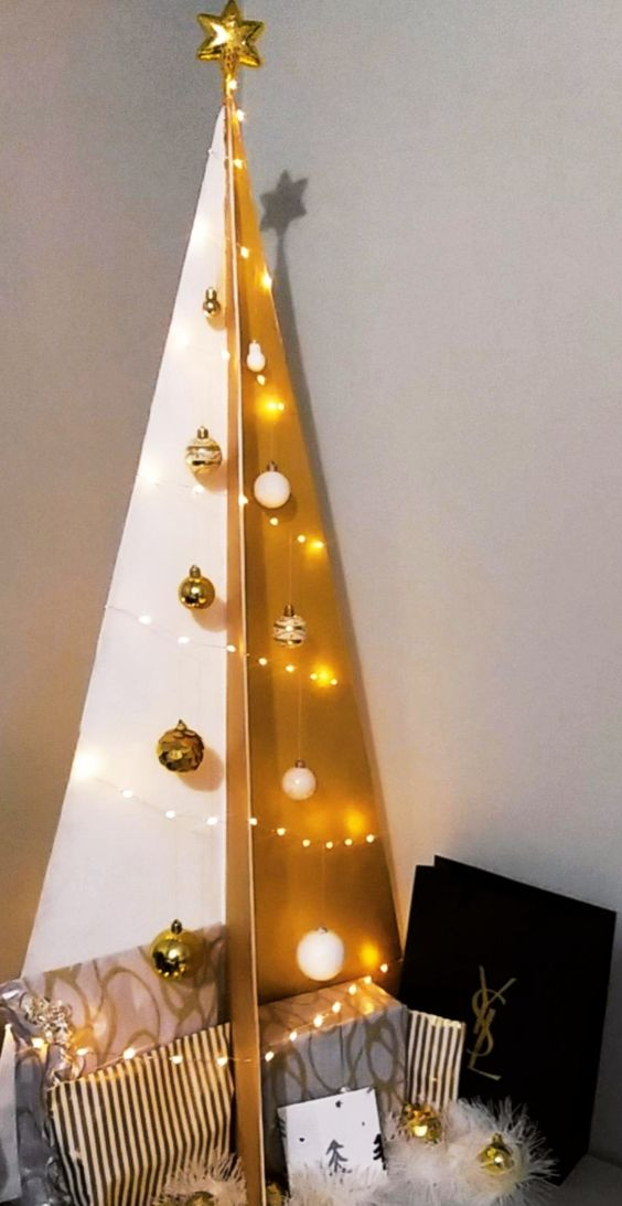 a 3D plywood Christmas tree in gold and white, with lights and matching ornaments looks very chic and very glam
