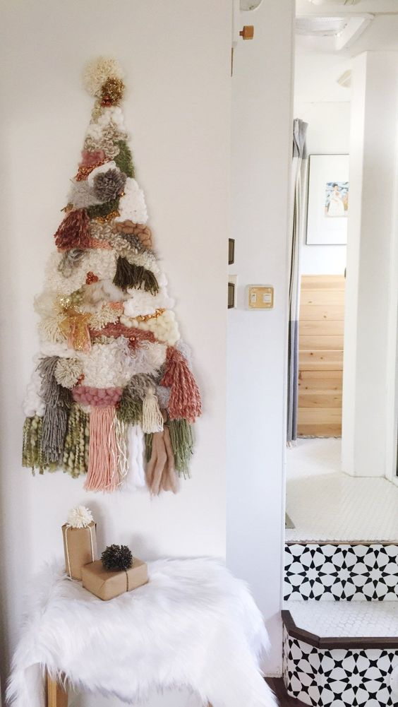 a creative tassel, pompom and yarn Christmas tree on the wall is a nice alternative for a boho space, if you don't have a nook for a real tree