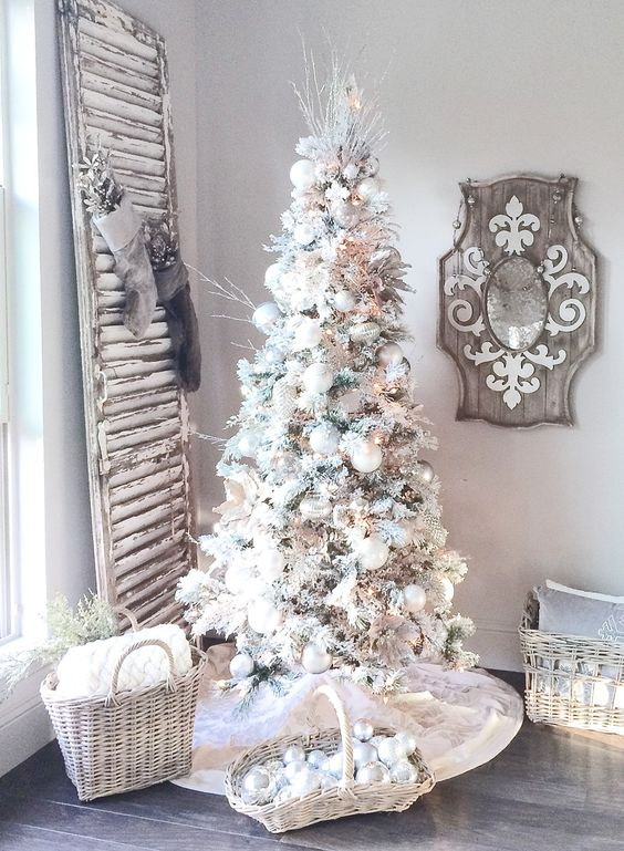 a flocked Christmas tree with white and silver ornaments, frosted twigs, pinecones and paper garlands and ornaments