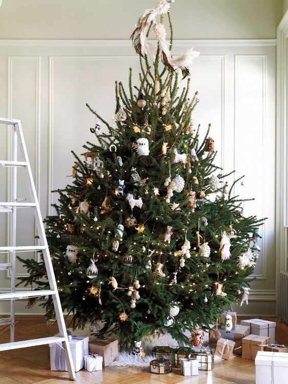 a stylish Christmas tree decorated with lights, with gold and white ornaments and feathers looks cool and wild