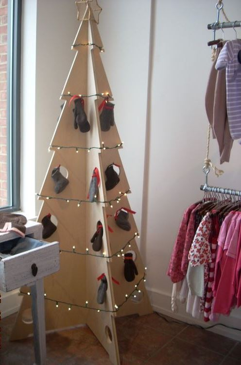 a 3D plywood Christmas tree with lights and stockings and mittens instead of usual ornaments