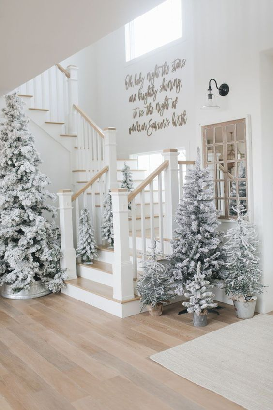 a gorgeous Christmas entryway with a whole cluster of flocked Christmas trees in buckets is a real winter wonderland