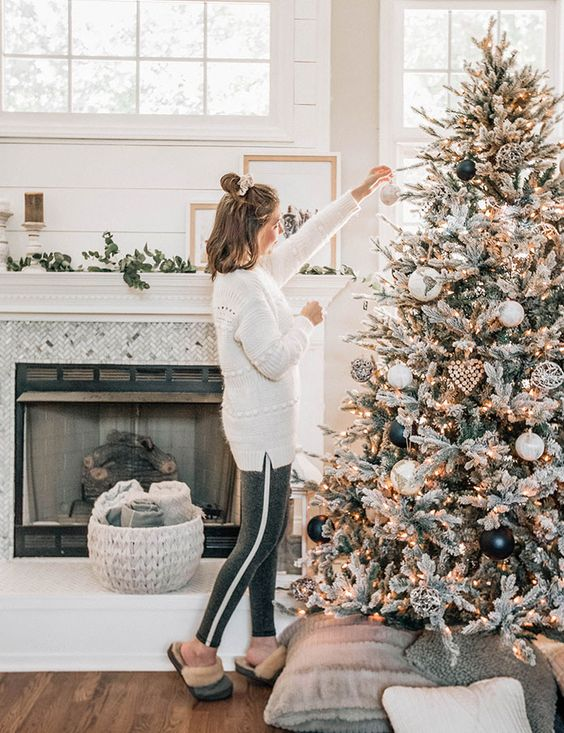 a stylish flocked Christmas tree with lights, white and metallic plus black ornaments and some rustic wooden ones