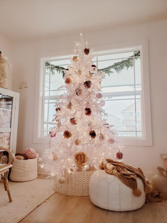 a white Christmas tree decorated with fluffy pompoms of earthy colors and put into a basket to make it look a bit rustic