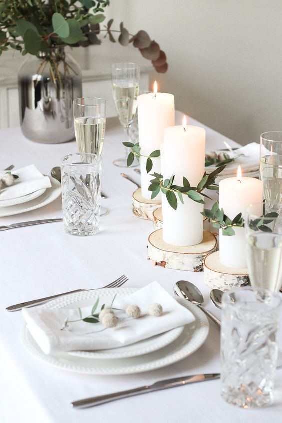 a beautiful white Christmas tablescape with wood slices, white porcelain, silver cutlery, elegant glasses, candles and some greenery