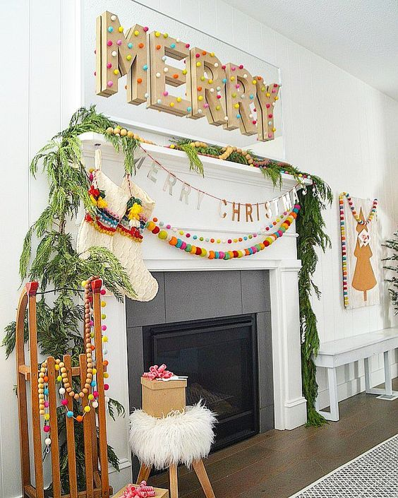 a colorful and fun boho Christmas fireplace and mantel with fir branches, colorful pompoms and a large sign with letters