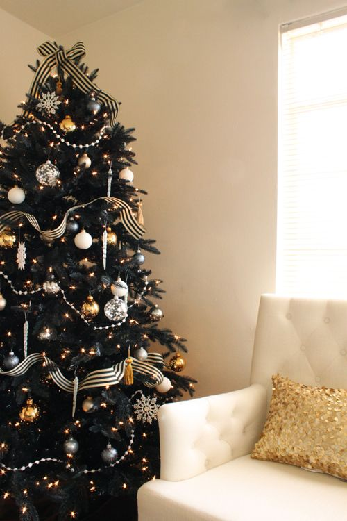 a refined black Christmas tree with lights, striped ribbon, silver and gold ornaments and striped bows is wow