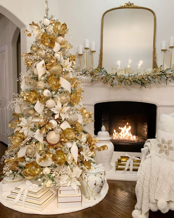 a very elegant and lush Christmas tree with large ornaments, berry twigs, ribbons and fabric blooms