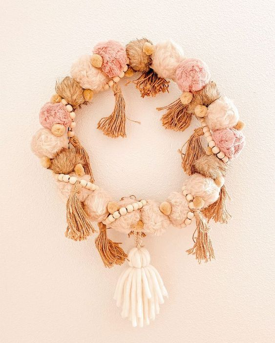 a beautiful pastel boho Christmas wreath of pompoms, tassels, wooden beads and a larger tassel piece as an accent
